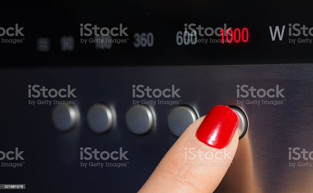 Turning on the microwave on maxium power stock photo