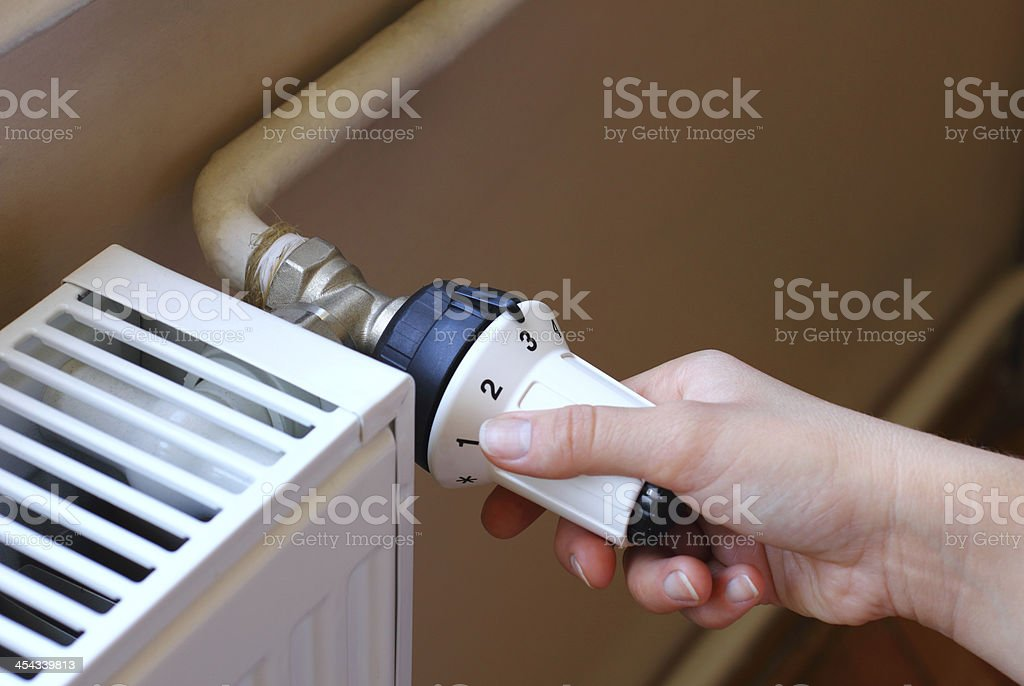 Turning on the radiator to save energy stock photo