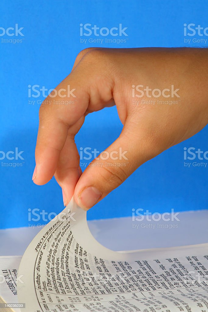 turning the bible page on blue royalty-free stock photo