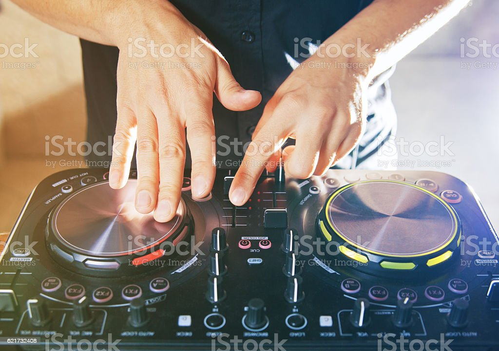 DJ turntable console mixer controlling stock photo