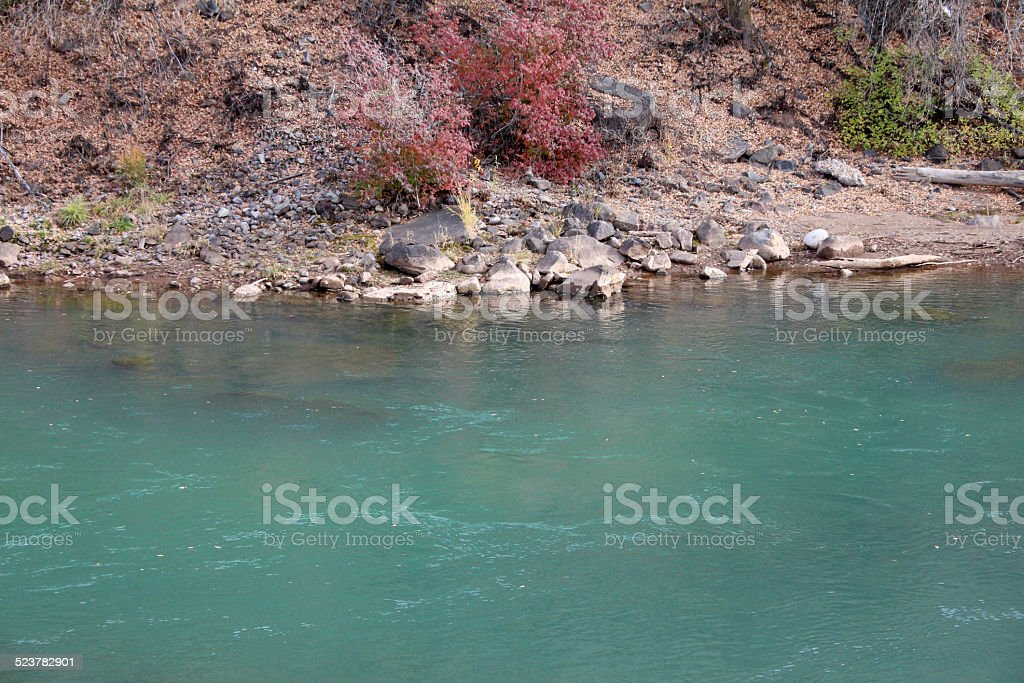 Turqouise river,rocky bank and fall colors stock photo