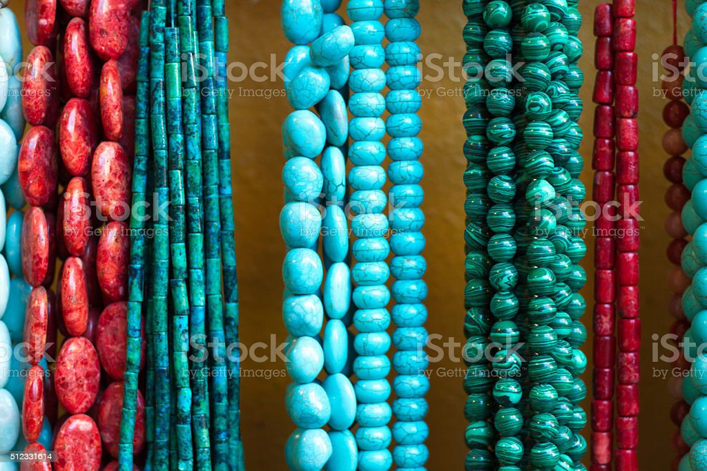 Turquoise and Coral Beads and Necklaces Hanging (Close-Up) stock photo