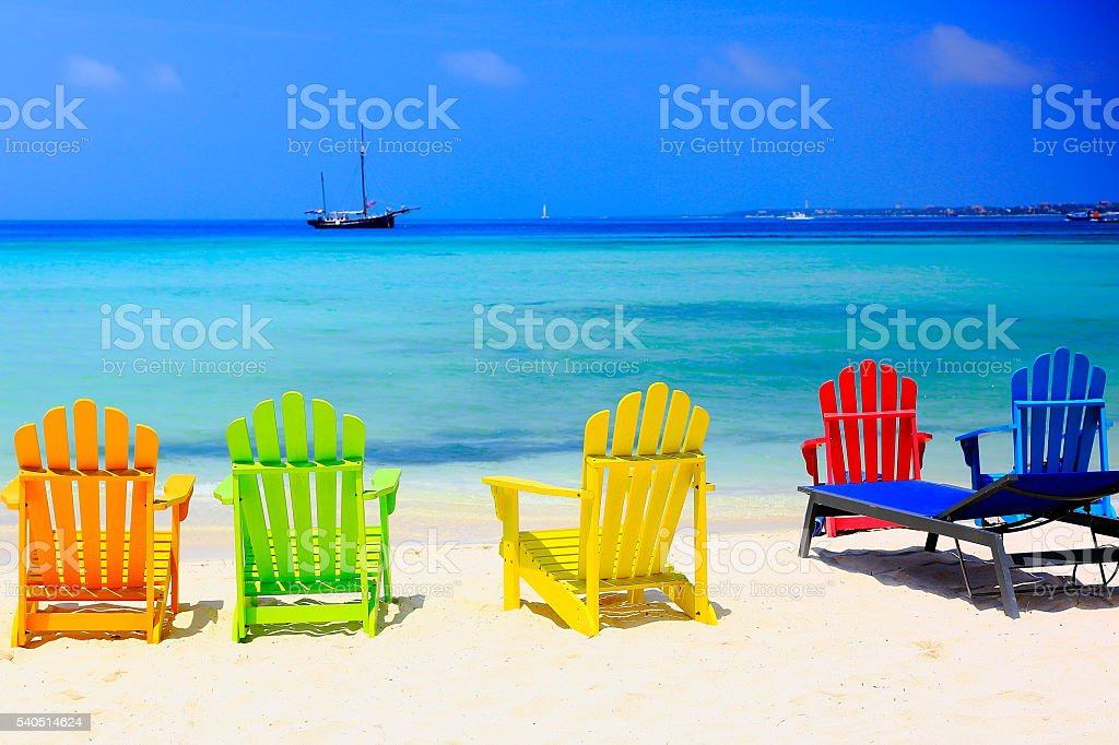 Turquoise bright beach, colorful chairs – Aruba turquoise caribbean tropical paradise stock photo