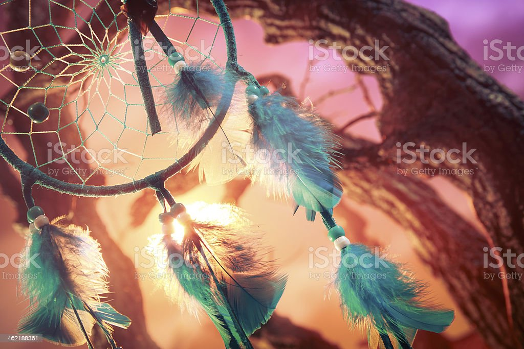 A turquoise dream catcher on a forest at sunset stock photo
