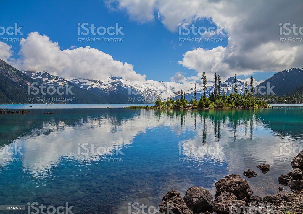 Turquoise Garibaldi Lake reflects mountains & trees, Whistler stock photo