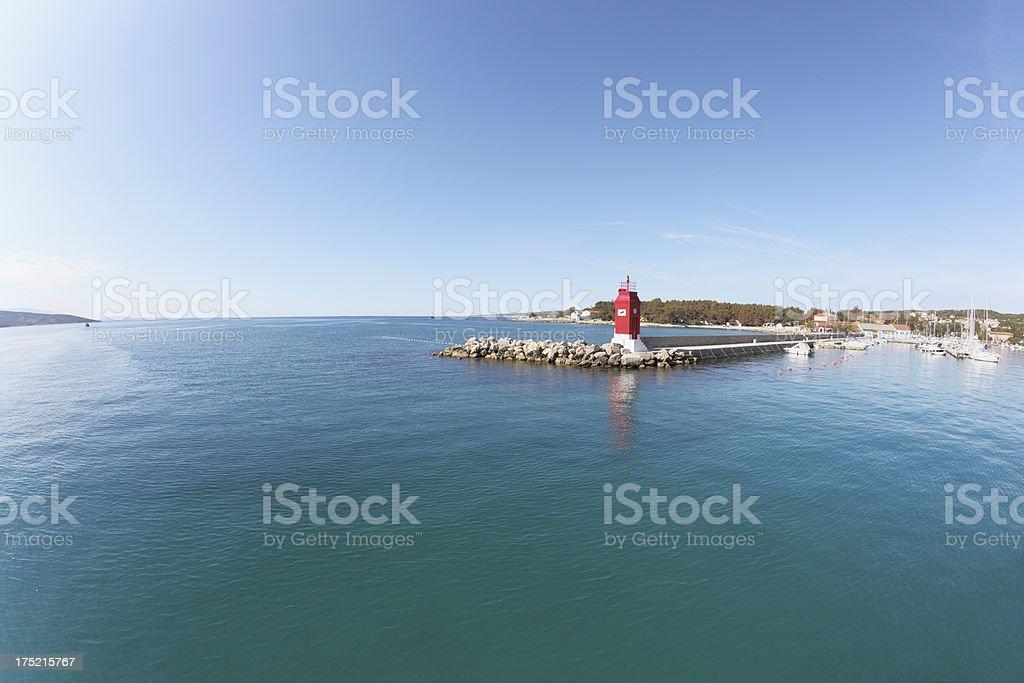 turquoise mediterranean ocean with beacon in Krk harbour Croatia royalty-free stock photo