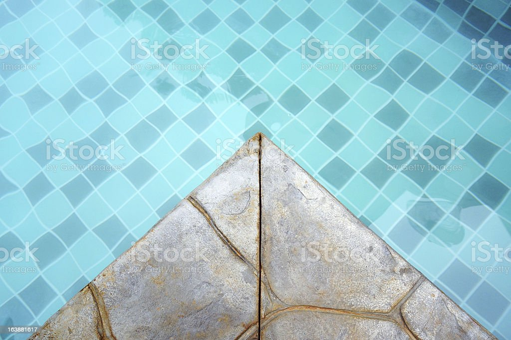 Turquoise mosaic tile in a swimming pool with stone edge royalty-free stock photo