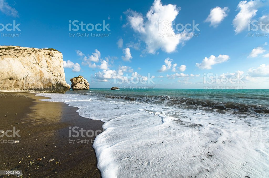 Turquoise ocean and blue sky with rocky cliff in background stock photo