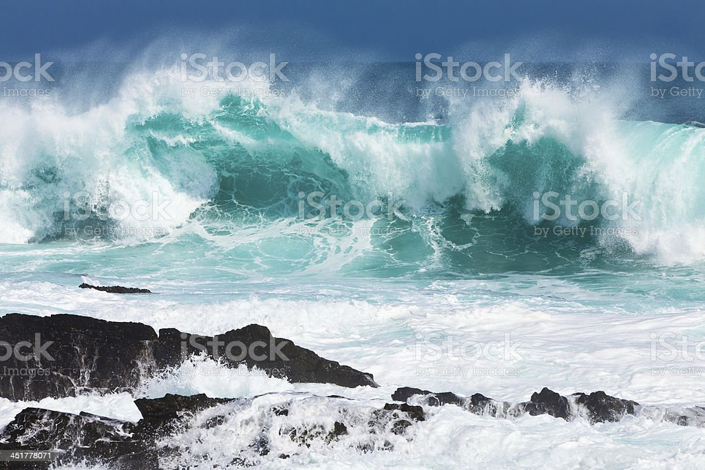 Turquoise rolling wave slaming on the rocks stock photo
