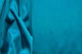 Turquoise silk background. Abstract wavy texture