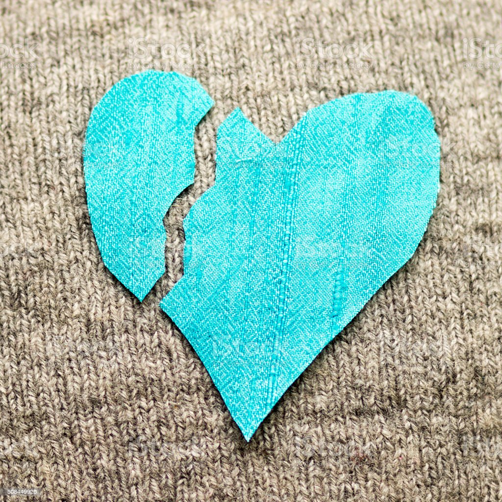 Turquoise silk broken heart on grey knitted background stock photo