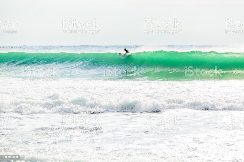 Turquoise wave in ocean and Sun rays stock photo
