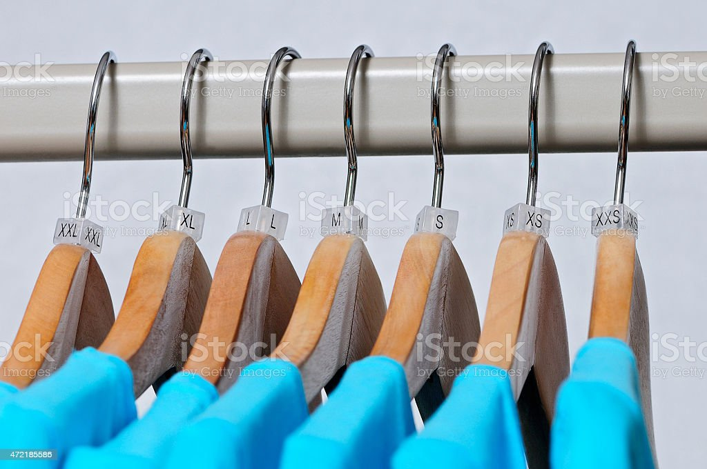 Turquoise women's t-shirts of various sizes hanging on wooden ha stock photo