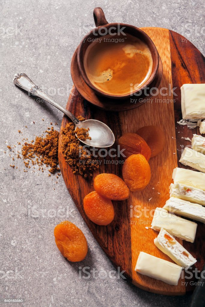 Turrón sliced on a wooden board with dried apricots, dried stock photo