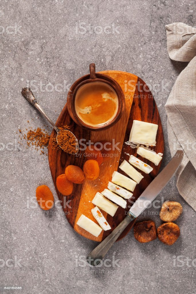 Turron sliced on a wooden board with dried apricots, dried stock photo
