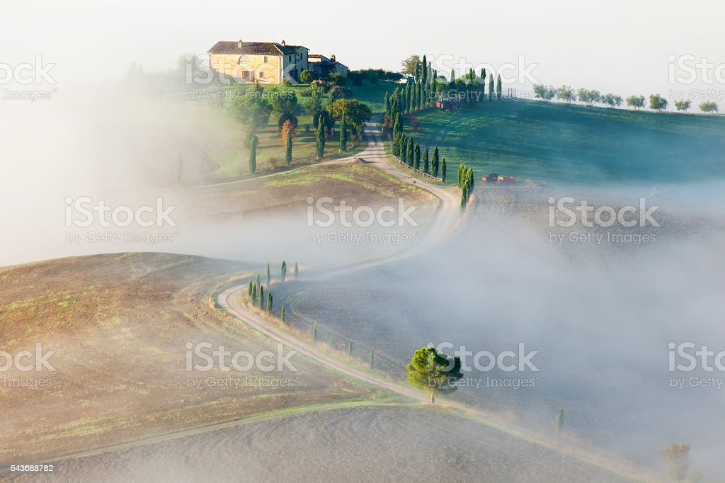 Tuscan Landscape With Country Road And Morning Fog stock photo