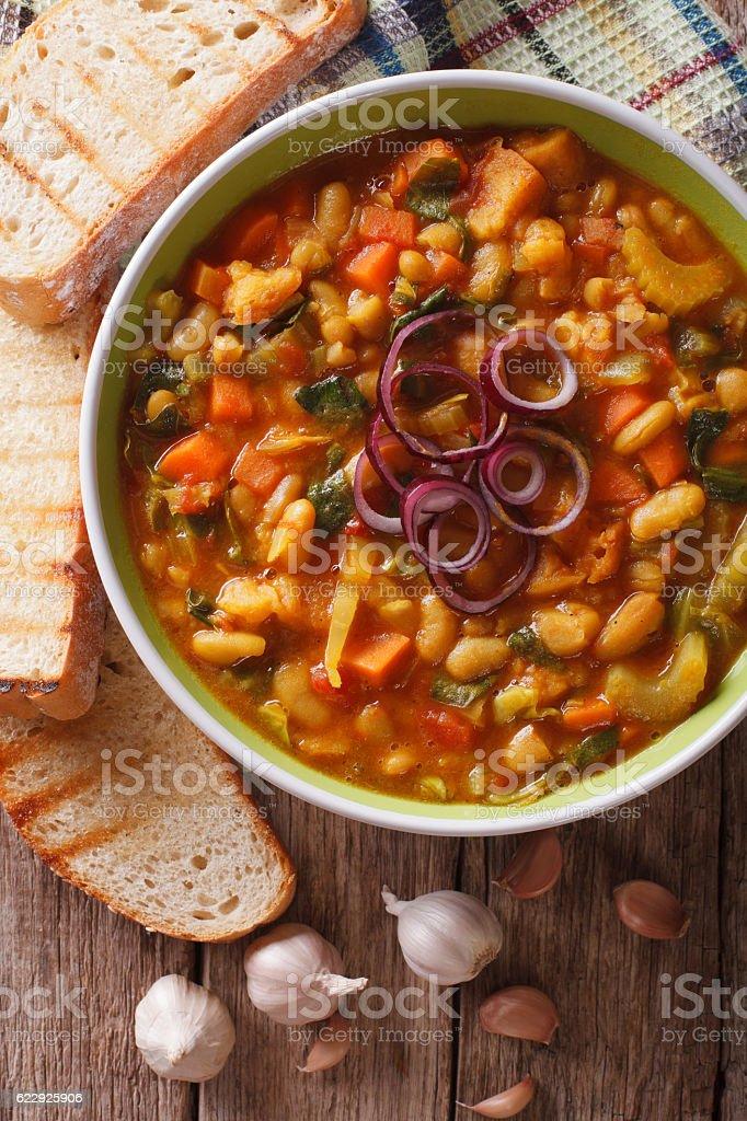 Tuscan ribollita soup closeup in a bowl. Vertical top view stock photo