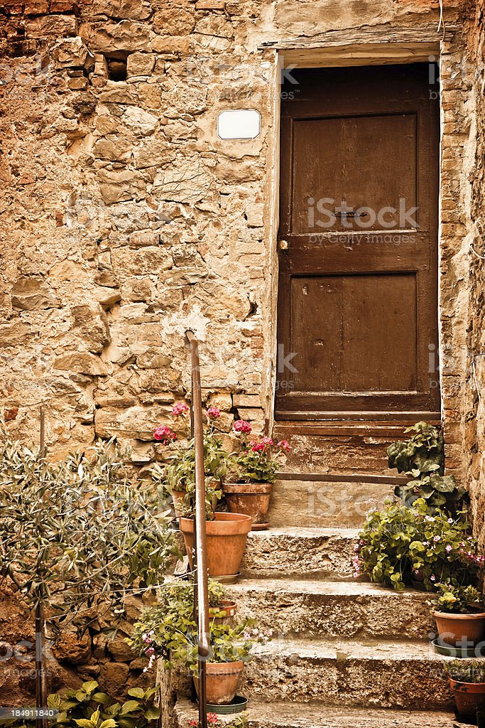 Tuscan Wooden Door with Small Plants, Val d'Orcia in Italy royalty-free stock photo