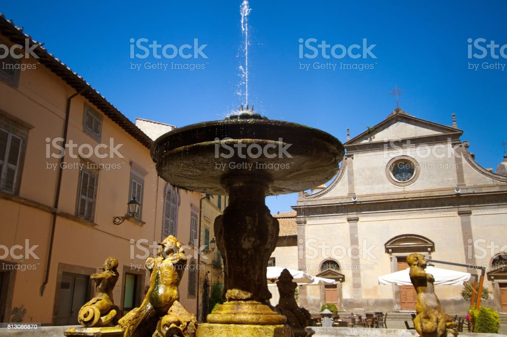Tuscania (Lazio), Italy: Main Piazza with Fountain and Church stock photo