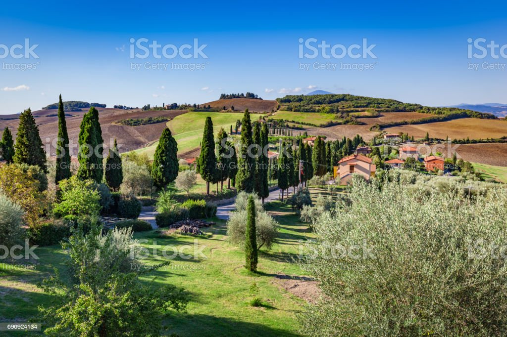 Tuscany countryside landscape with cypress trees, farms and green fields, Italy. stock photo