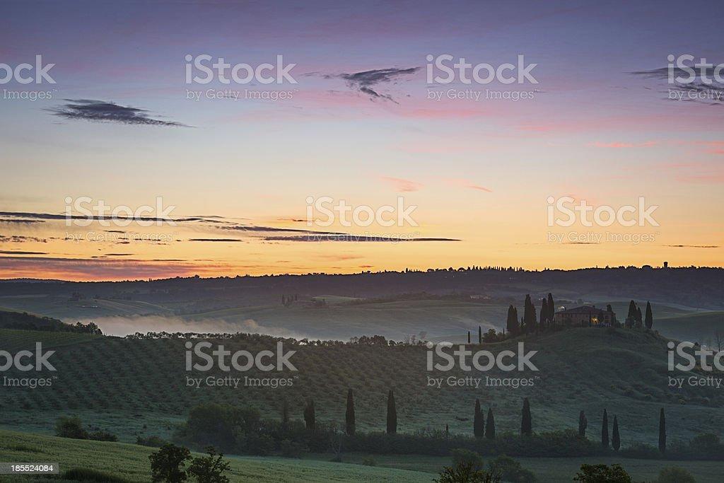 Tuscany farmhouse with vibrant sky at dawn, Val d'Orcia, Italy royalty-free stock photo