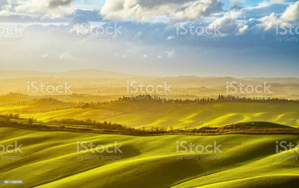 Tuscany misty panorama at sunset, rolling hills, fields, meadow. Italy stock photo