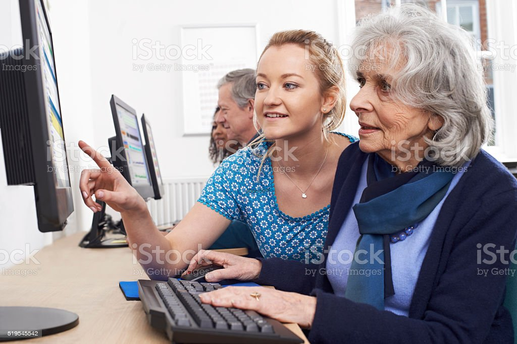 Tutor Helping Senior Woman In Computer Class stock photo