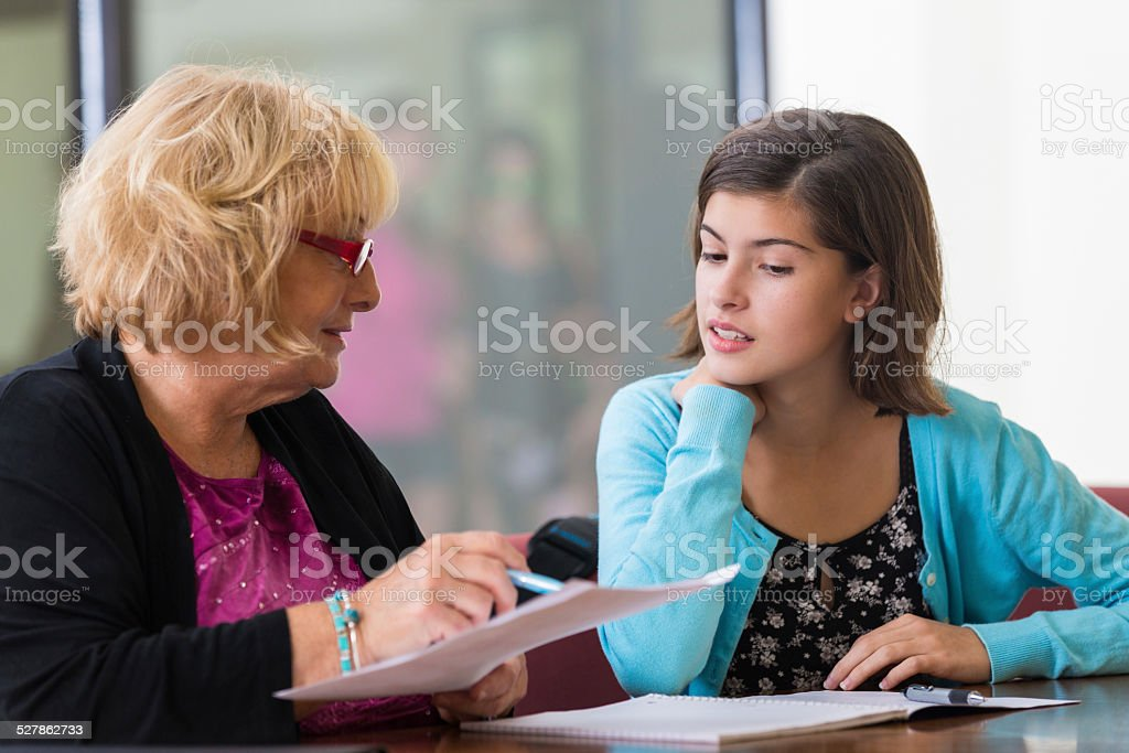 Tutor or school counselor meeting with junior high student stock photo