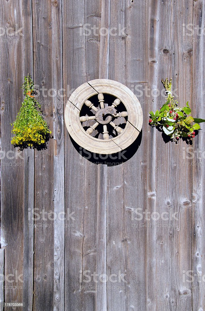 tutsan and raspberry bunches with wheel on wall royalty-free stock photo