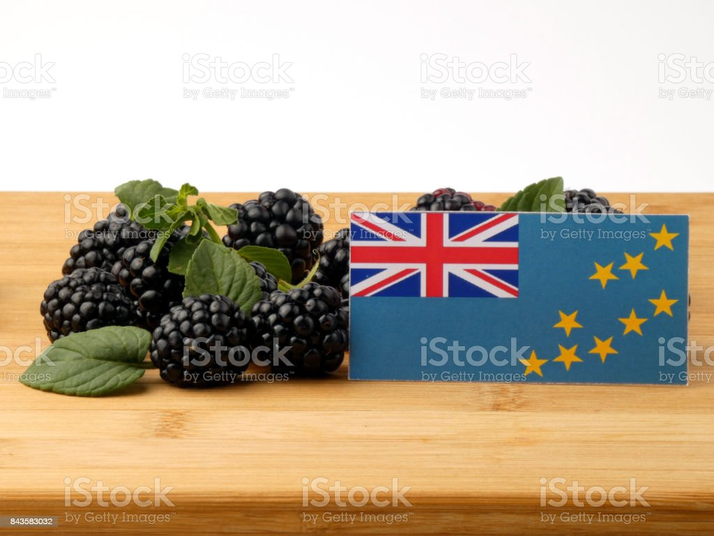 Tuvalu flag on a wooden panel with blackberries isolated on a white background stock photo