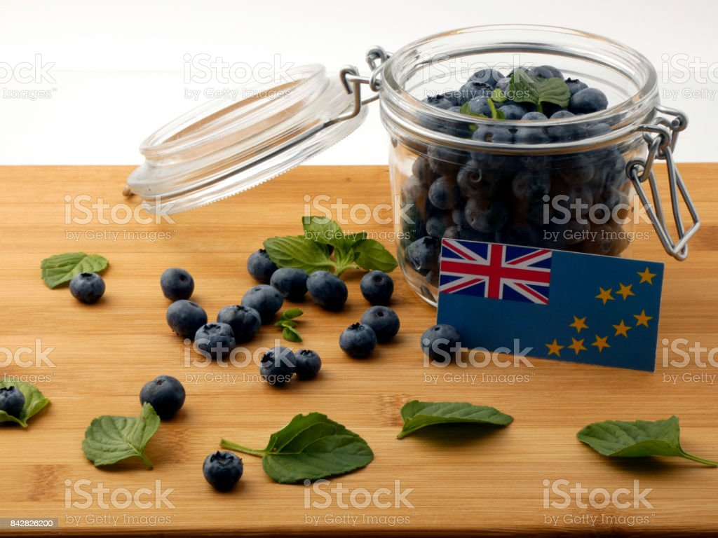 Tuvalu flag on a wooden plank with blueberries isolated on white stock photo