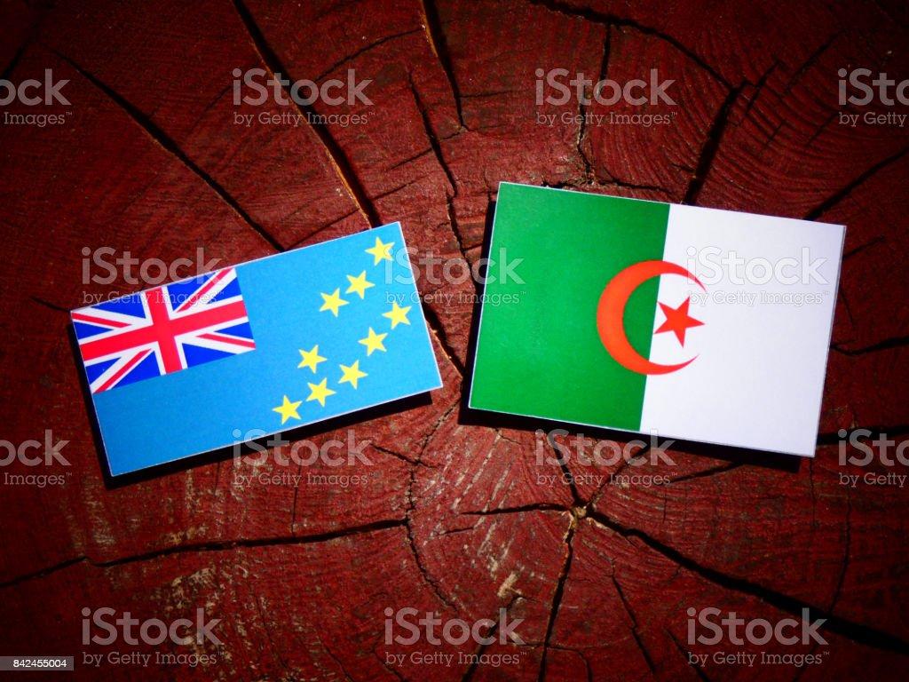 Tuvalu flag with Algerian flag on a tree stump isolated stock photo