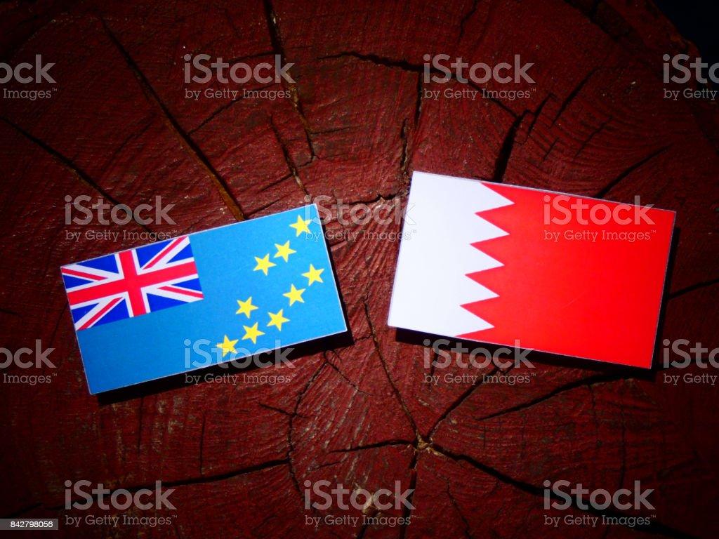 Tuvalu flag with Bahraini flag on a tree stump isolated stock photo
