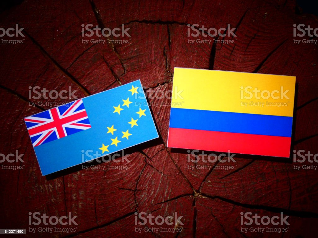 Tuvalu flag with Colombian flag on a tree stump isolated stock photo