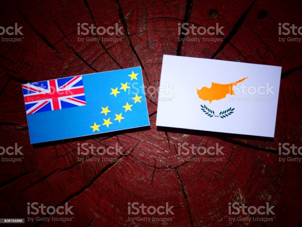 Tuvalu flag with Cypriot flag on a tree stump isolated stock photo