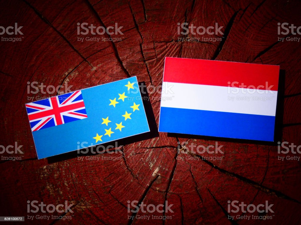 Tuvalu flag with Dutch flag on a tree stump isolated stock photo