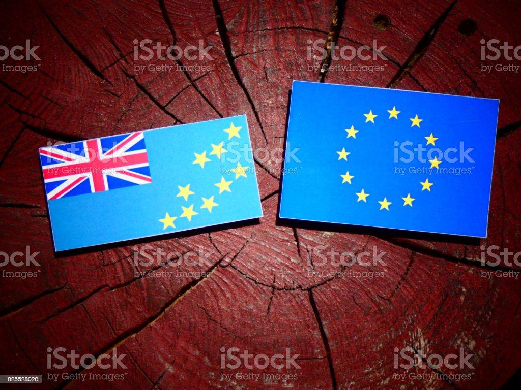Tuvalu flag with EU flag on a tree stump isolated stock photo