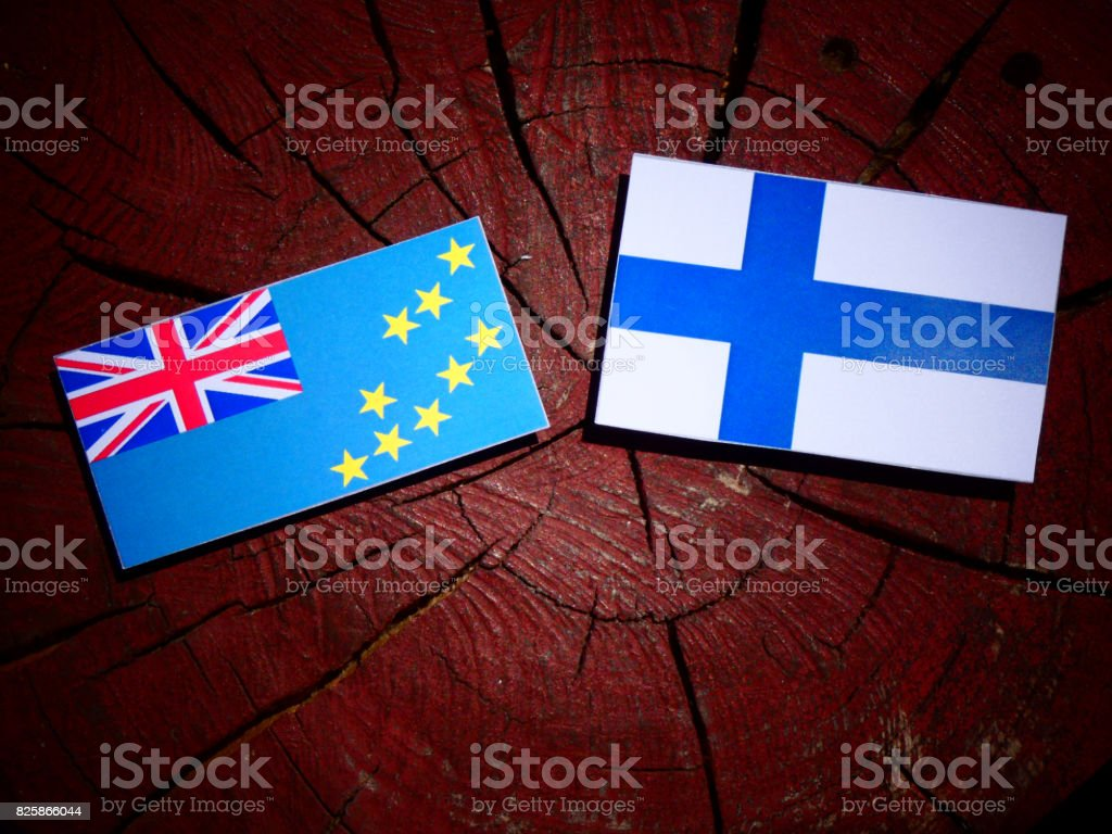 Tuvalu flag with Finnish flag on a tree stump isolated stock photo
