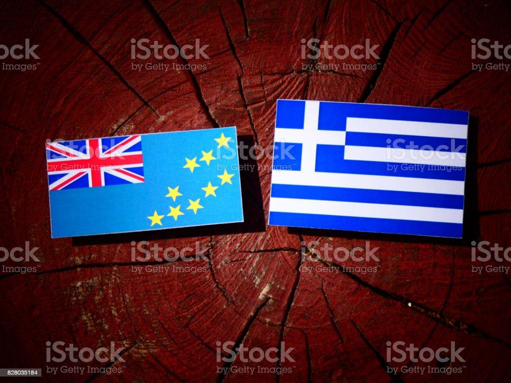 Tuvalu flag with Greek flag on a tree stump isolated stock photo