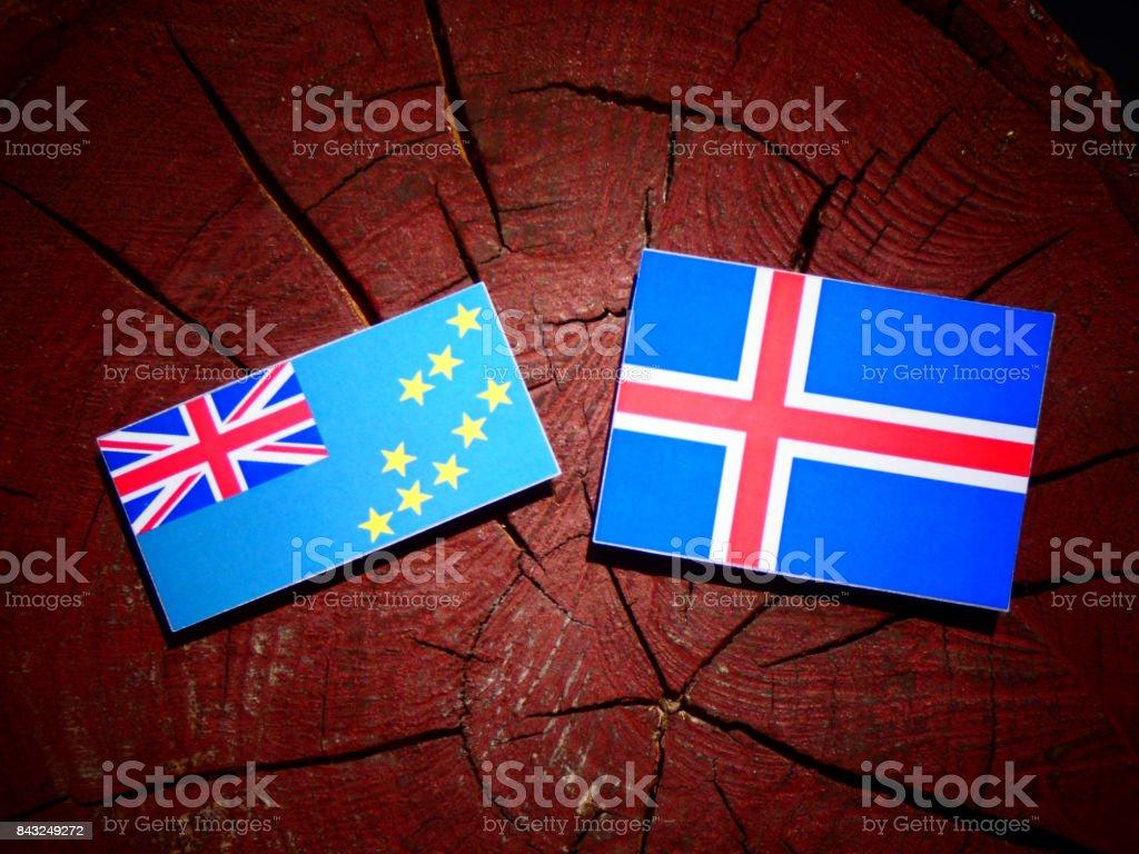 Tuvalu flag with Icelandic flag on a tree stump isolated stock photo