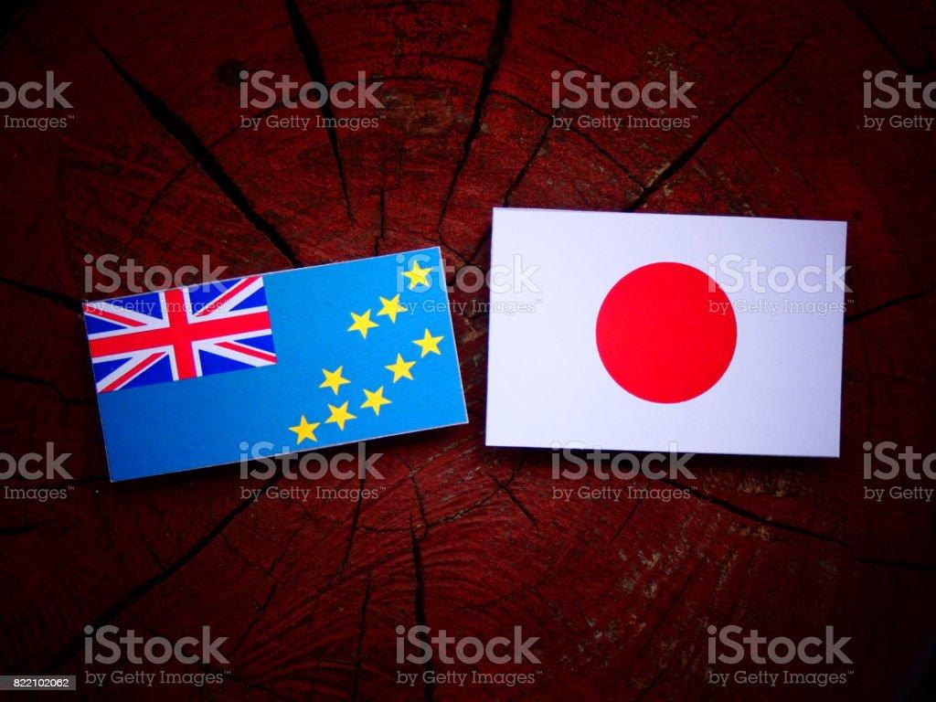 Tuvalu flag with Japanese flag on a tree stump isolated stock photo