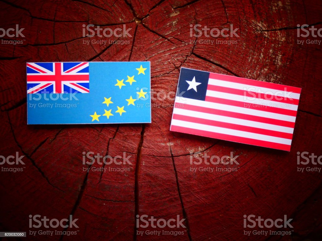 Tuvalu flag with Liberian flag on a tree stump isolated stock photo
