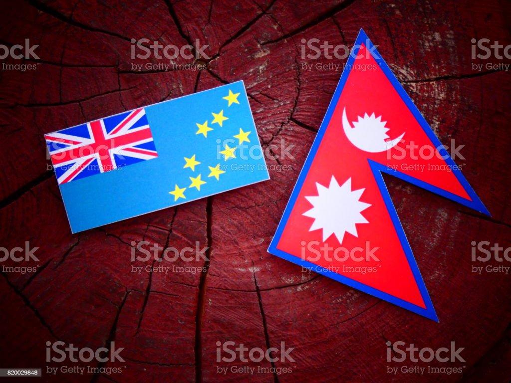 Tuvalu flag with Nepali flag on a tree stump isolated stock photo