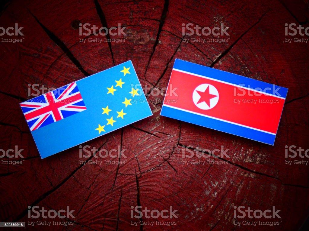 Tuvalu flag with North Korean flag on a tree stump isolated stock photo