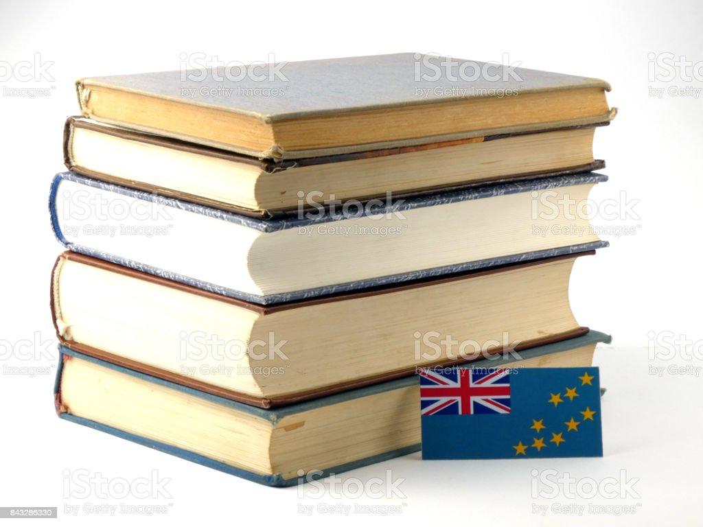 Tuvalu flag with pile of books isolated on white background stock photo