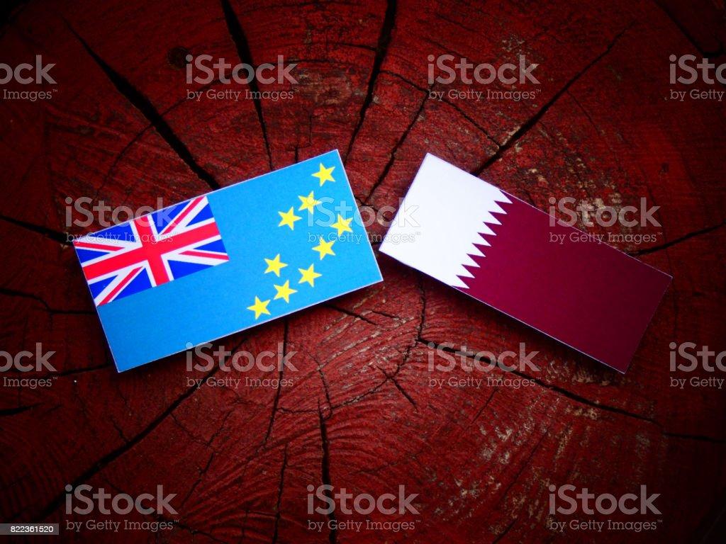Tuvalu flag with Qatari flag on a tree stump isolated stock photo