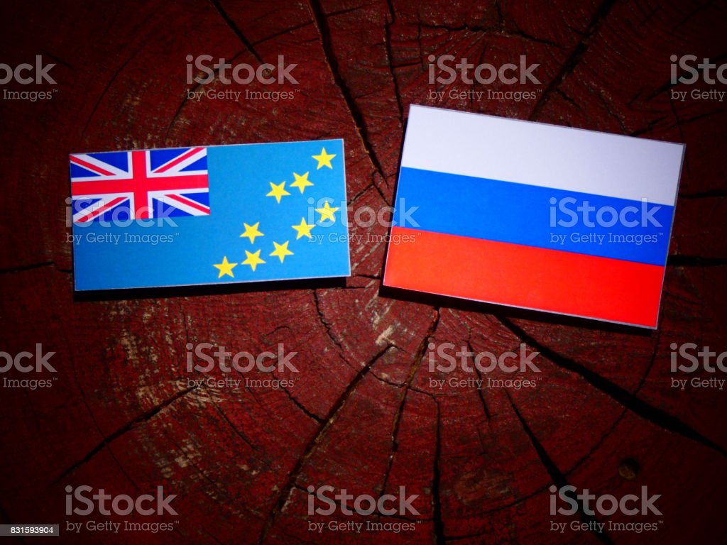 Tuvalu flag with Russian flag on a tree stump isolated stock photo