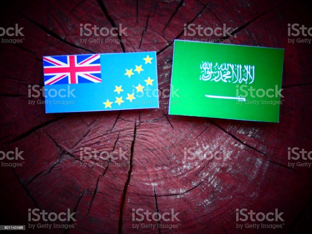 Tuvalu flag with Saudi Arabian flag on a tree stump isolated stock photo