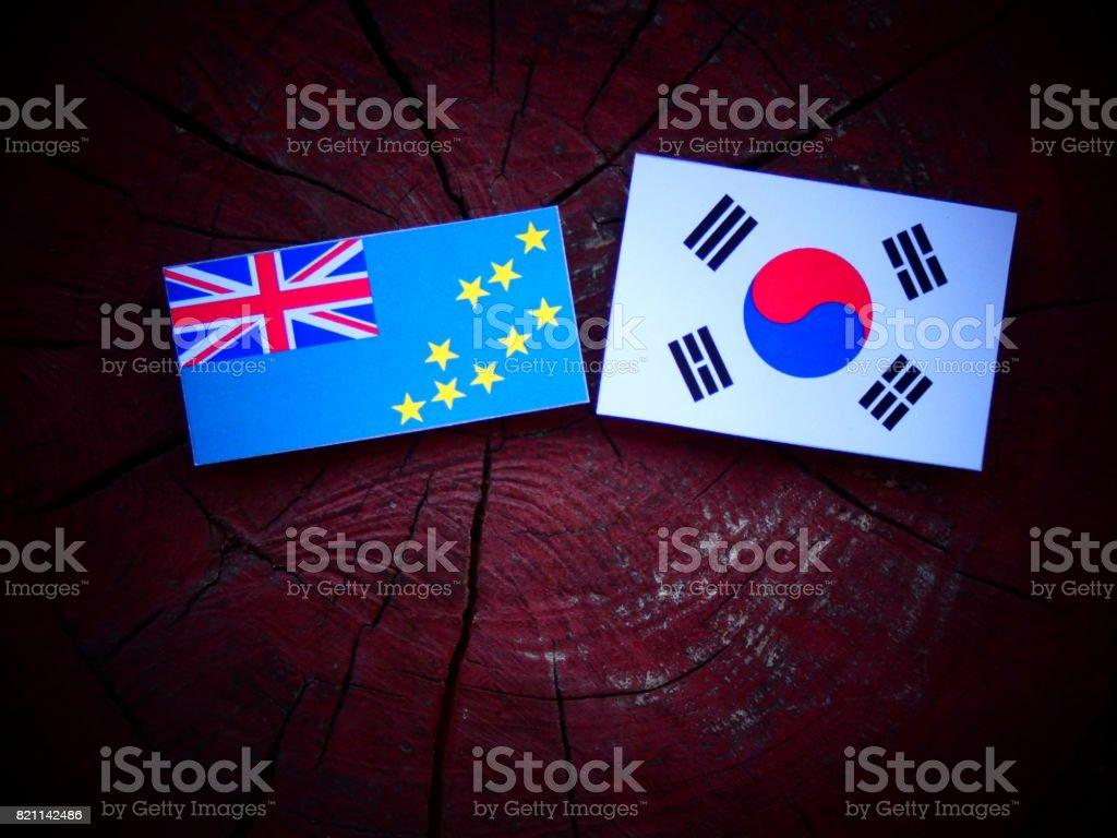 Tuvalu flag with South Korean flag on a tree stump isolated stock photo