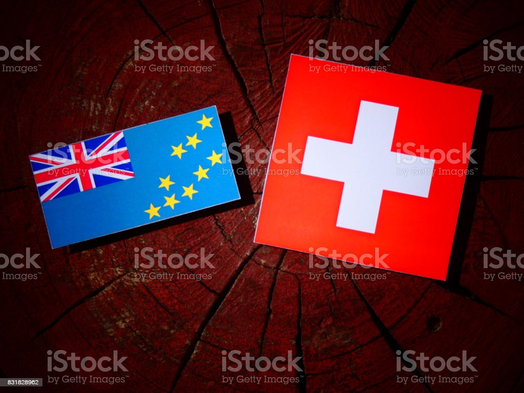 Tuvalu flag with Swiss flag on a tree stump isolated stock photo